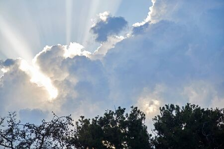 blue sky with sunbeams and clouds.