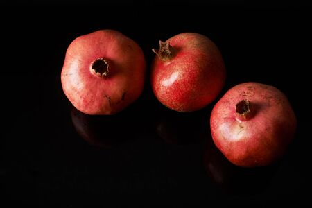 pomegranate fruits on black background.