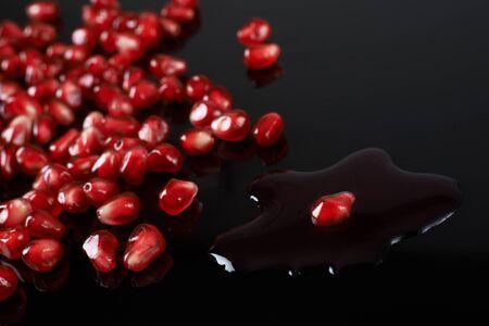 pomegranate seeds and juice on black background. Reklamní fotografie
