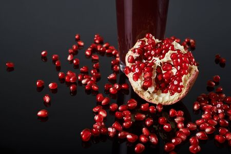 pomegranate fruit, seeds and juice on black background. Reklamní fotografie