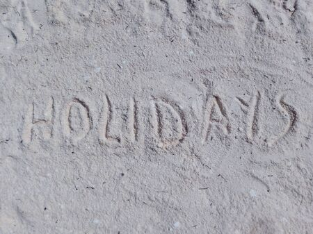 the word holidays written on the sand of a beach.