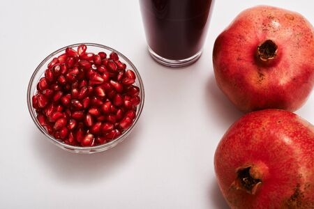pomegranate fruits, seeds and juice on white background.