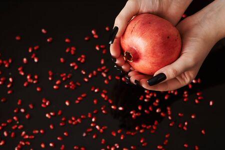 hands holding a pomegranate fruite on black background full of seeds.