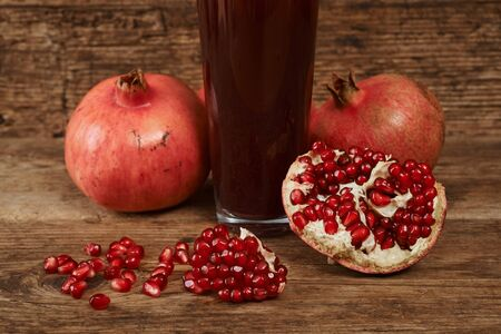 ripe pomegranate fruits with glass of juice on wooden table.