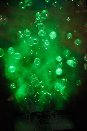 Green soap bubbles at night as background.Texture.