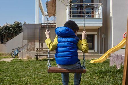 kid in swings in the garden. Standard-Bild