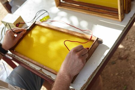beekeeper make honeycomb for his apiary. Standard-Bild