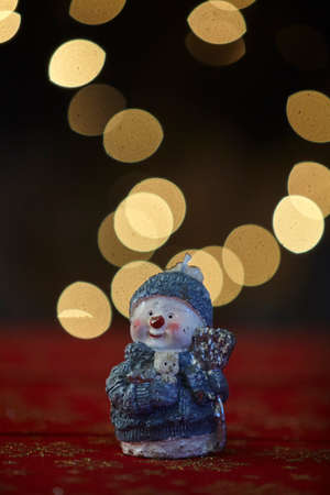 Christmas snowman ornament on lights background.