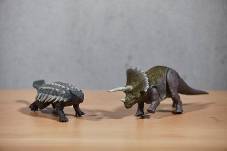 Dinosaur toys on wooden table.