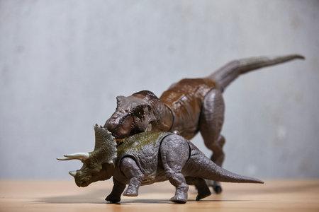 Dinosaur t-rex toys on wooden table.