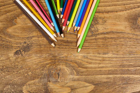 colored pencils on wooden table.