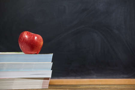red apple and books  on wooden table and blackdoard background.school for kids. Standard-Bild