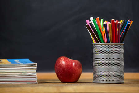 red apple, books and penciles on wooden table and blackdoard background.school for kids.