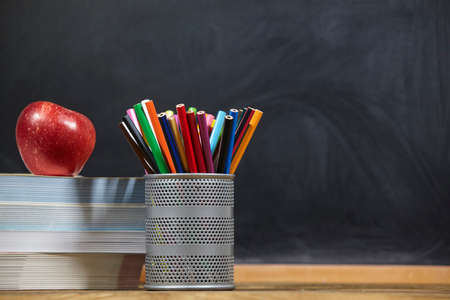 red apple, books and penciles on wooden table and blackdoard background.school for kids. Standard-Bild - 161618698