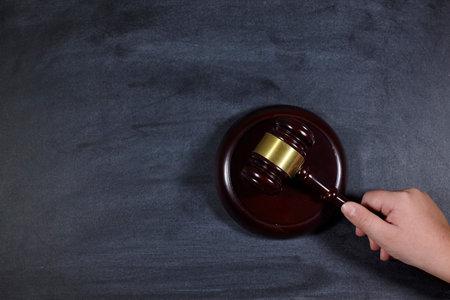 man holds court gavel on blackboard. judgment. Standard-Bild