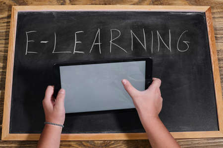 kid holding a tablet on wooden table. e-learning school.