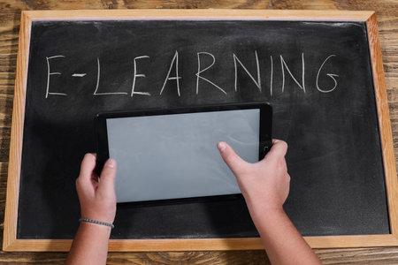 kid holding a tablet on wooden table. e-learning school. Standard-Bild - 161618875