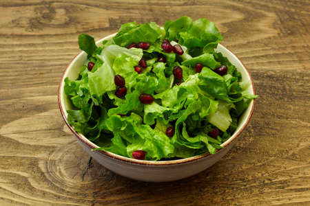 green salad and pomegranate on wooden table. healthy diet.
