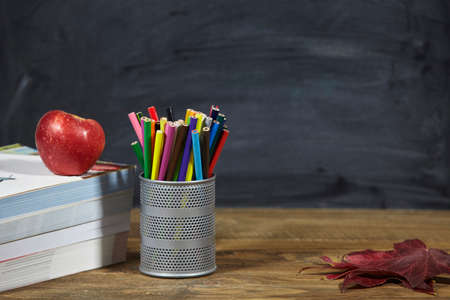 red apple, books, red leaves and penciles on wooden table and blackdoard background.school for kids.