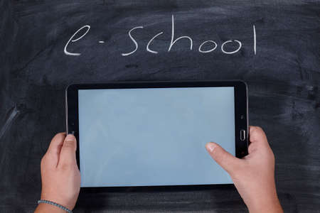 kid holding a tablet on wooden table. e-learning school. Standard-Bild - 161619069