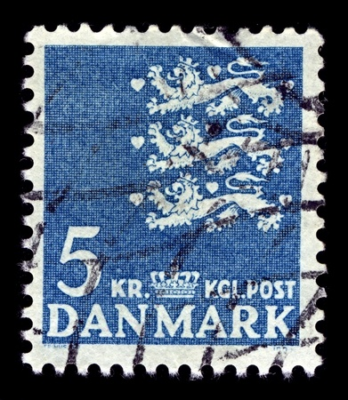 perforated stamp: Denmark-CIRCA 1946:A stamp printed in Denmark shows image of The national coat of arms of Denmark consists of three crowned blue lions accompanied by nine red hearts, all in a golden shield, circa 1946. Editorial