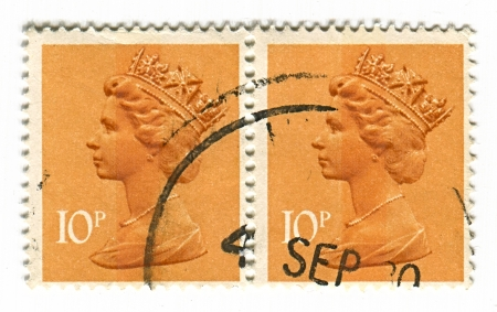 realms: UK-CIRCA 1980:A stamp printed in UK shows image of Elizabeth II is the constitutional monarch of 16 sovereign states known as the Commonwealth realms, head of the 54-member Commonwealth of Nations, in orange, circa 1980. Editorial