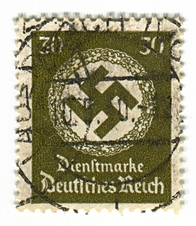 hitler: GERMANY - CIRCA 1937: A stamp printed in Germany shows image of the swastika  is an equilateral cross with four arms bent at right angles, in green, circa 1937.