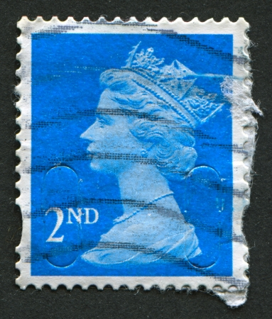realms: UK-CIRCA 1989:A stamp printed in UK shows image of Elizabeth II is the constitutional monarch of 16 sovereign states known as the Commonwealth realms, in blue, circa 1989.