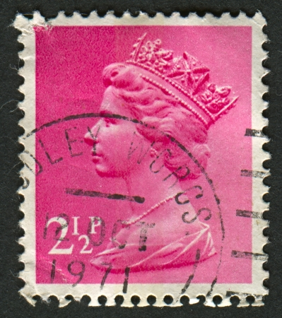 realms: UK-CIRCA 1971:A stamp printed in UK shows image of Elizabeth II is the constitutional monarch of 16 sovereign states known as the Commonwealth realms, in pink, circa 1971. Editorial