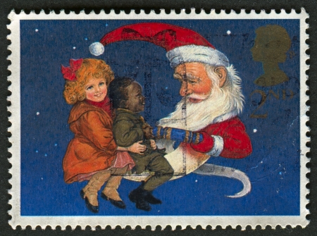 UK - CIRCA 1997: A stamp printed in UK shows image of The Children and Father Christmas pulling Cracker, 150th Anniversary of the Christmas Cracker, circa 1997.