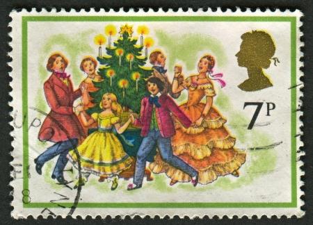 carols: UK - CIRCA 1978: A stamp printed in UK shows image of The Singing Carols round the Christmas Tree, circa 1978.  Editorial