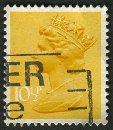 realms: UK-CIRCA 1976:A stamp printed in UK shows image of Elizabeth II is the constitutional monarch of 16 sovereign states known as the Commonwealth realms, in yellow, circa 1976. Editorial