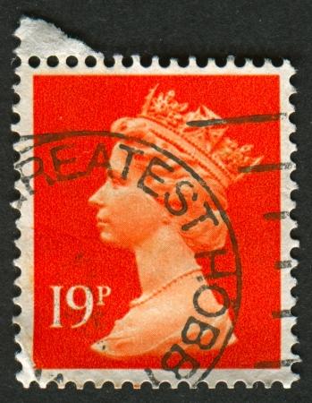 definitive: Reino Unido-alrededor de 1988: Un sello impreso en Reino Unido muestra imagen de Isabel II es el monarca constitucional de 16 estados soberanos conocidos como los reinos de la Commonwealth, en rojo, alrededor de 1988.