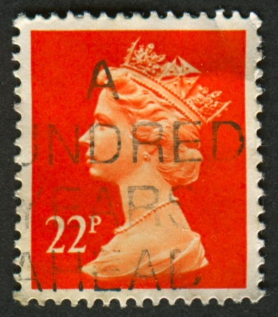 realms: UK-CIRCA 1990:A stamp printed in UK shows image of Elizabeth II is the constitutional monarch of 16 sovereign states known as the Commonwealth realms, in red, circa 1990.