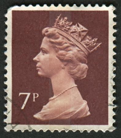 definitive: Reino Unido-alrededor de 1975: Un sello impreso en Reino Unido muestra imagen de Isabel II es el monarca constitucional de 16 estados soberanos conocidos como los reinos de la Commonwealth, en p?rpura Brown, alrededor de 1975.
