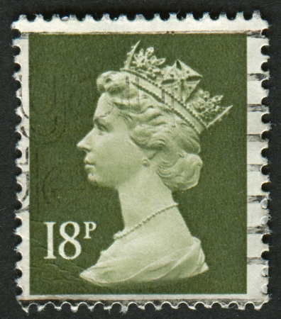 realms: UK-CIRCA 1984:A stamp printed in UK shows image of Elizabeth II is the constitutional monarch of 16 sovereign states known as the Commonwealth realms, in Deep Olive Grey, circa 1984.
