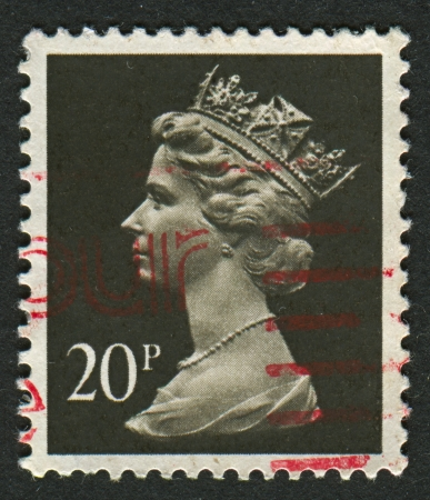 realms: UK-CIRCA 1990:A stamp printed in UK shows image of Elizabeth II is the constitutional monarch of 16 sovereign states known as the Commonwealth realms, in Brownish Black and Cream, circa 1990.
