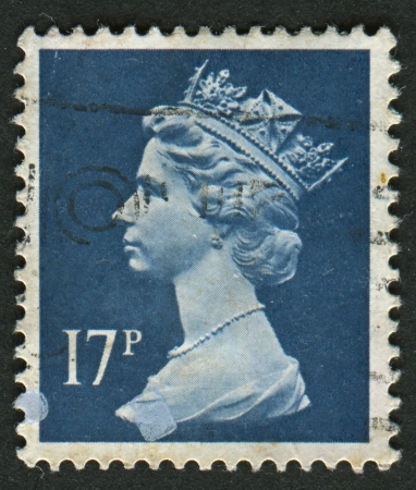 realms: UK-CIRCA 1990:A stamp printed in UK shows image of Elizabeth II is the constitutional monarch of 16 sovereign states known as the Commonwealth realms, in Deep Blue, circa 1990. Editorial