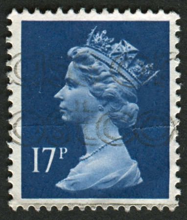 definitive: UK-CIRCA 1990:A stamp printed in UK shows image of Elizabeth II is the constitutional monarch of 16 sovereign states known as the Commonwealth realms, in Deep Blue, circa 1990. Editorial