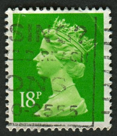 definitive: Reino Unido-alrededor de 1991: Un sello impreso en Reino Unido muestra imagen de Isabel II es el monarca constitucional de 16 estados soberanos conocidos como los reinos de la Commonwealth, en verde claro, alrededor de 1991.