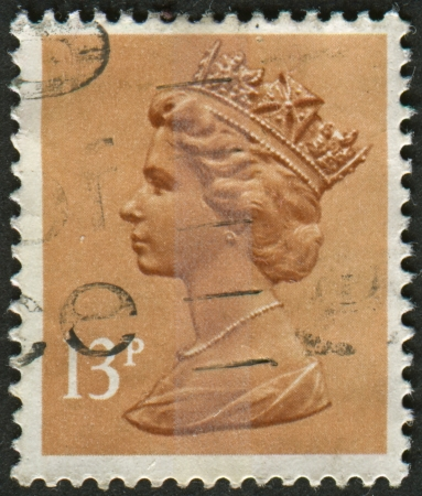 realms: UK-CIRCA 1984:A stamp printed in UK shows image of Elizabeth II is the constitutional monarch of 16 sovereign states known as the Commonwealth realms, in Pale Chestnut, circa 1984.