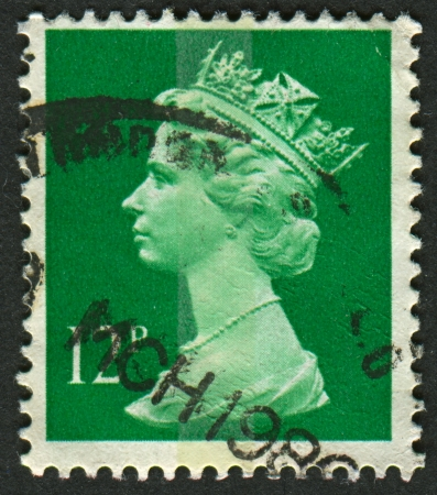 UK-CIRCA 1985: A stamp printed in UK shows image of Elizabeth II is the constitutional monarch of 16 sovereign states known as the Commonwealth realms, in Bright Emerald, circa 1985.