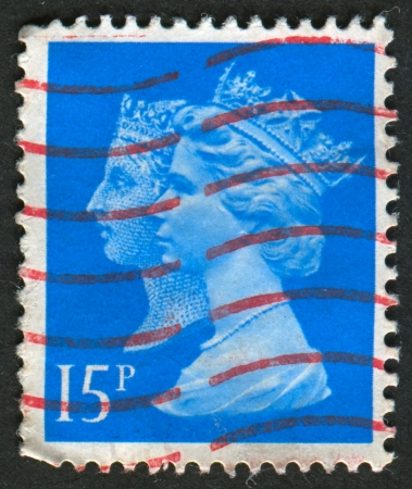 realms: UK-CIRCA 1989: A stamp printed in UK shows image of Elizabeth II is the constitutional monarch of 16 sovereign states known as the Commonwealth realms, in Deep Bright Blue, circa 1989. Editorial