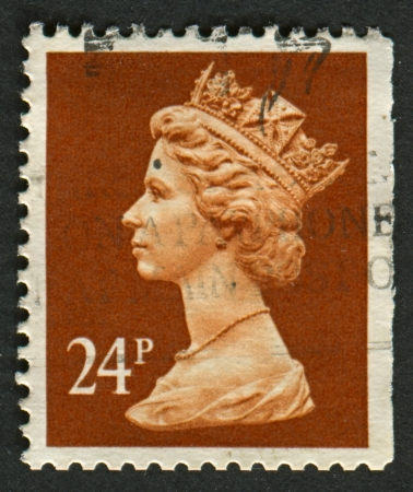realms: UK-CIRCA 1989: A stamp printed in UK shows image of Elizabeth II is the constitutional monarch of 16 sovereign states known as the Commonwealth realms, in Indian Red, circa 1989.