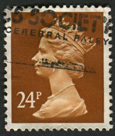 indian postal stamp: UK-CIRCA 1989: A stamp printed in UK shows image of Elizabeth II is the constitutional monarch of 16 sovereign states known as the Commonwealth realms, in Indian Red, circa 1989.