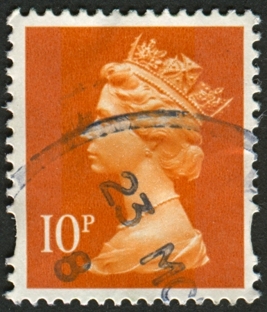 realms: UK-CIRCA 1993: A stamp printed in UK shows image of Elizabeth II is the constitutional monarch of 16 sovereign states known as the Commonwealth realms, in dull orange, circa 1993.
