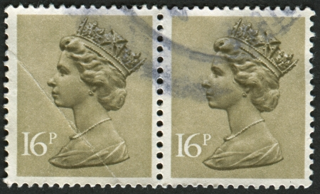 realms: UK-CIRCA 1983: A stamp printed in UK shows image of Elizabeth II is the constitutional monarch of 16 sovereign states known as the Commonwealth realms, in Olive Drab, circa 1983.