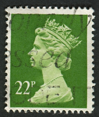 realms: UK-CIRCA 1984: A stamp printed in UK shows image of Elizabeth II is the constitutional monarch of 16 sovereign states known as the Commonwealth realms, in Yellow Green, circa 1984.