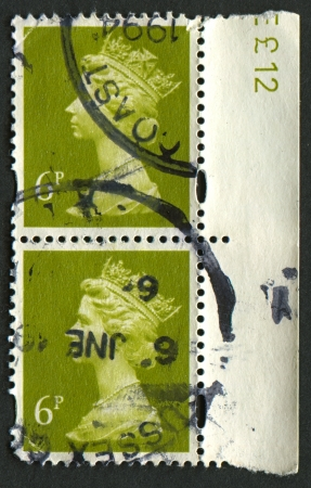 realms: UK-CIRCA 1991: A stamp printed in UK shows image of Elizabeth II is the constitutional monarch of 16 sovereign states known as the Commonwealth realms, in Yellow Olive, circa 1991. Editorial