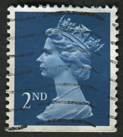 realms: UK-CIRCA 1993: A stamp printed in UK shows image of Elizabeth II is the constitutional monarch of 16 sovereign states known as the Commonwealth realms, in bright blue, circa 1993. Editorial